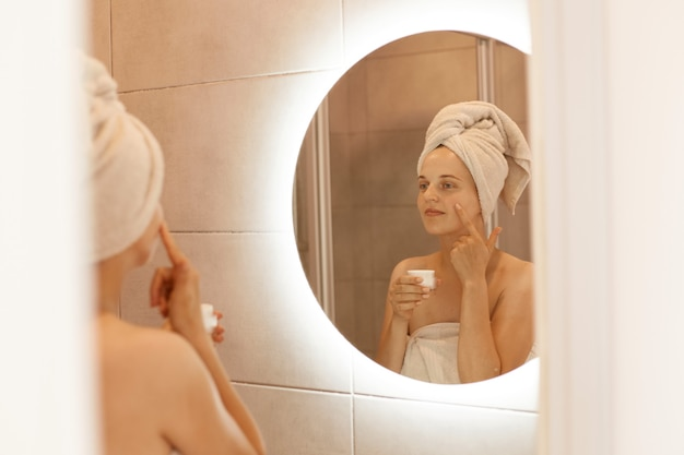 Odbicie kobiety w lustrze rozcierającej krem kosmetyczny na twarzy, nakładającej krem nawilżający na skórę twarzy w łazience, owiniętej białym ręcznikiem, wykonującej zabiegi upiększające.