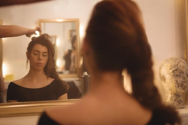 Odbicie kobiety w lustrze stylizującej włosy w salonie