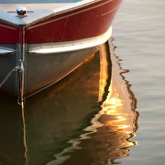 Odbicie łódź w wodzie przy jeziorem drewna, ontario