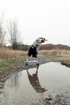 Odbicie męskiej sportowca w kałuży ćwiczeń
