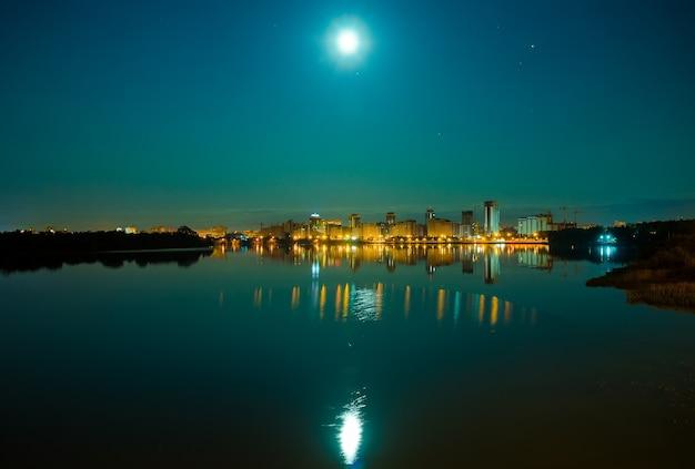 Odbicie miasta nocą na powierzchni wody.