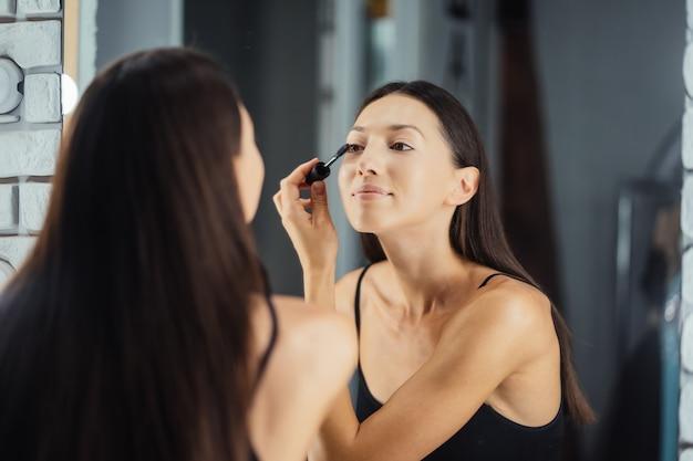 Odbicie młodej kobiety piękne, stosując makijaż, patrząc w lustro