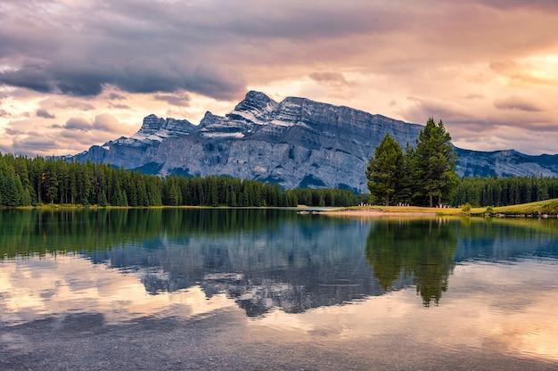 Odbicie mount rundle nad jeziorem two jack wieczorem w parku narodowym banff, kanada