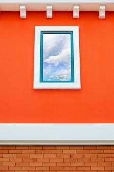 Odbicie nieba i chmur w szybie okiennej na pomarańczowej ścianie domu, włochy w stylu retro