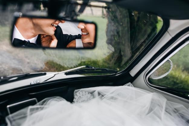 Odbicie nowożeńców uśmiechniętych twarzy w rzadkim oknie ok