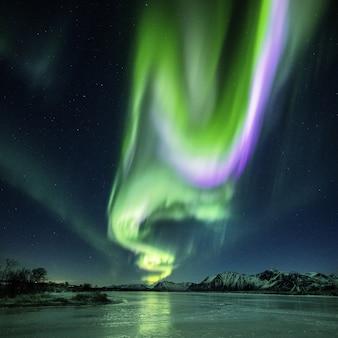 Odbicie pięknej zorzy polarnej w jeziorze nocą uchwycone w norwegii