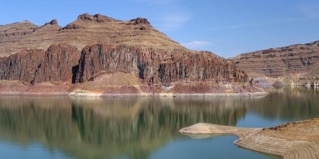Odbicie skalistych klifów w jeziorze pod niebieskim niebem