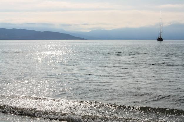Odbicie słońca w wodzie morskiej i sylwetka żaglowca na horyzoncie.