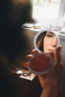 Odbicie twarzy pięknej kobiety w lustrze w jej ramionach