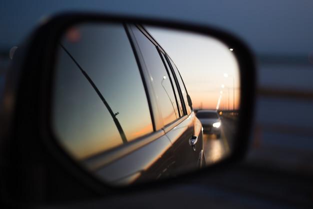 Odbicie w lustrze drogi samochodowej z transportem o zachodzie słońca