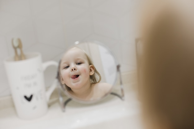 Odbicie w lustrze małej śmiesznej dziewczynki myjącej ręce i twarz w łazience