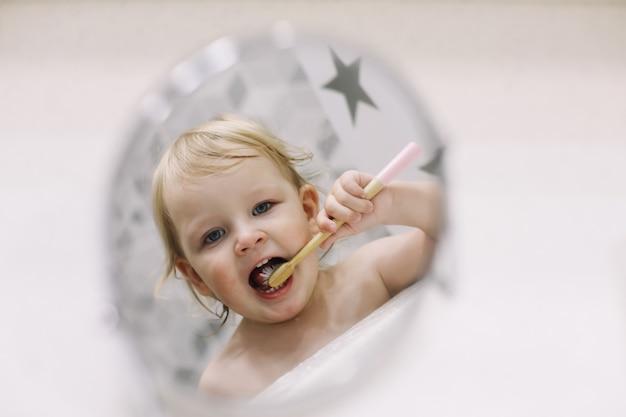 Odbicie w lustrze małej zabawnej dziewczynki myjącej zęby