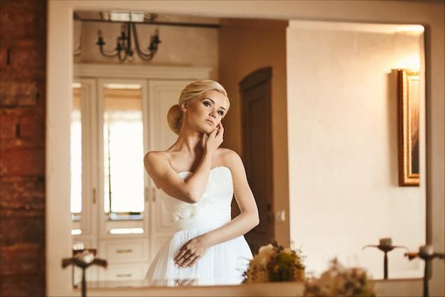 Odbicie w lustrze pięknej i modnej modelki o blond włosach z fryzurą ślubną w modnej sukni, rano przygotowanie młodej panny młodej do ślubu