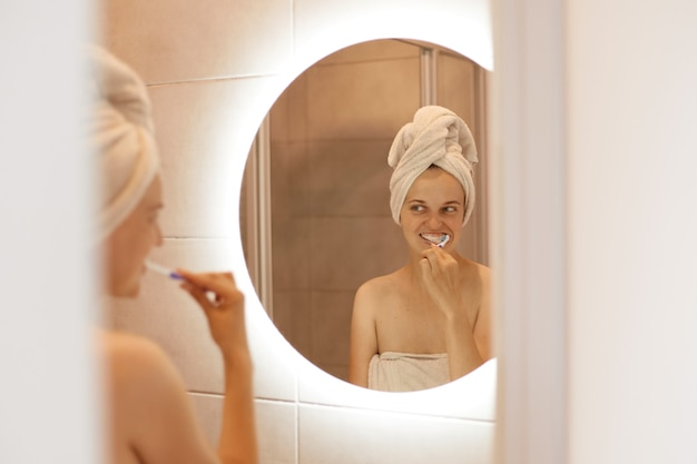 Odbicie w lustrze ujmującej młodej dorosłej kobiety z białym ręcznikiem na włosach pozuje w łazience i myje zęby, procedury higieniczne po wzięciu prysznica.