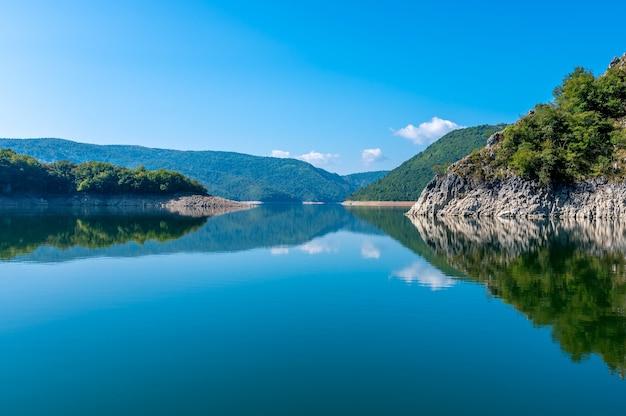 Odbicie wzgórz i lasu na jeziorze