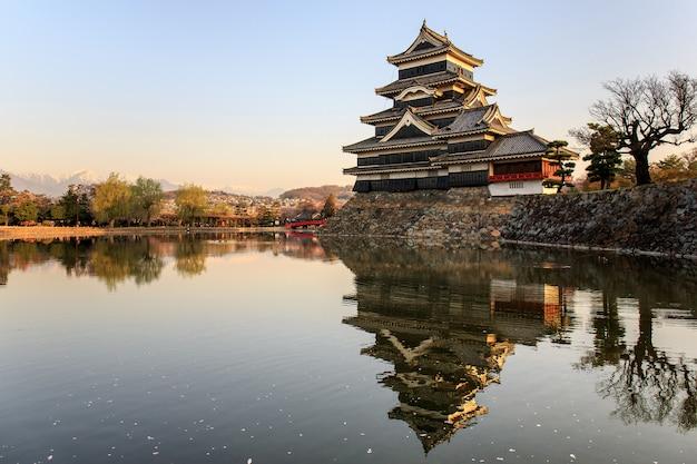 Odbicie zamku matsumoto z ciepłym światłem rano