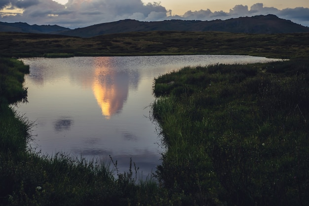 Odbicie żółtej dużej chmury w postaci eksplozji w górskim jeziorze. niesamowita gigantyczna chmura odbita w wodzie jeziora wśród zielonych traw o wschodzie słońca. ogromna chmura oświetlającego koloru na niebie gradientowym świtu.