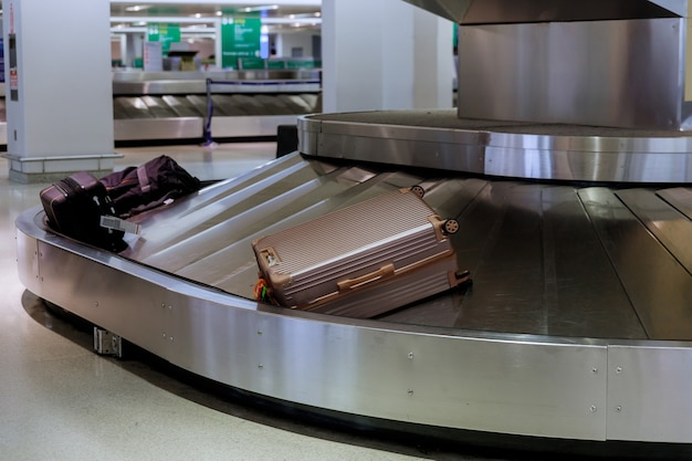 Odbiór bagażu w walizkach na taśmie bagażowej na lotnisku