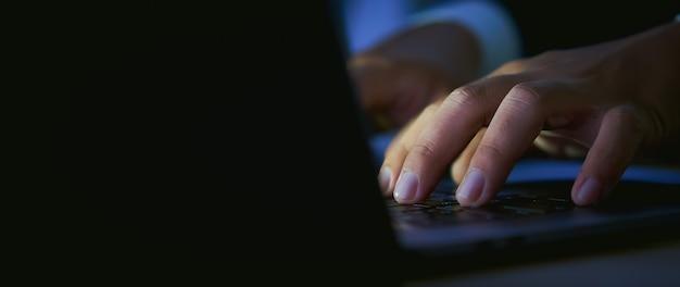 Odbitkowa przestrzeń biznesmen ręki używa komputerowego laptop z prasową klawiaturą przy biurem i nocą