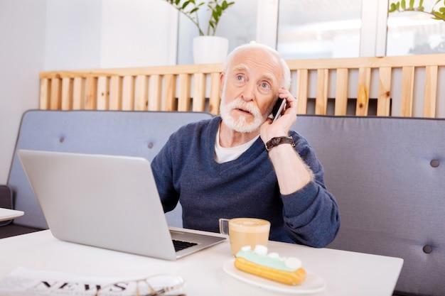 Odblaskowy starszy freelancer za pomocą laptopa i rozmawia przez telefon
