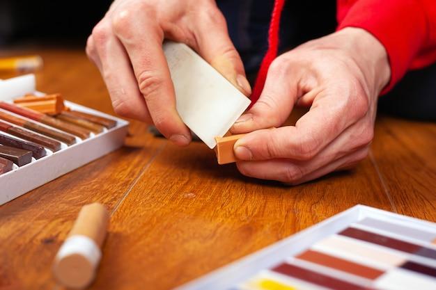 Odbudowa laminatu i parkietu uszczelniająca rysy i wióry. master naprawia drewnianą powierzchnię z bliska ołówkami woskowymi.