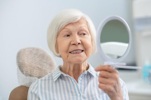 Odbudowa zębów. starsza kobieta patrząca w lustro po wizycie w gabinecie dentystycznym