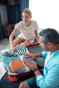 Odchodzić. poważna kobieta siedzi z mężem na łóżku i pomaga mu pakować walizkę podróżną.