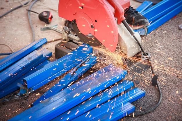 Odcięte koło tnące przecina kwadratową rurę ze stali nierdzewnej, tak jak iskry.