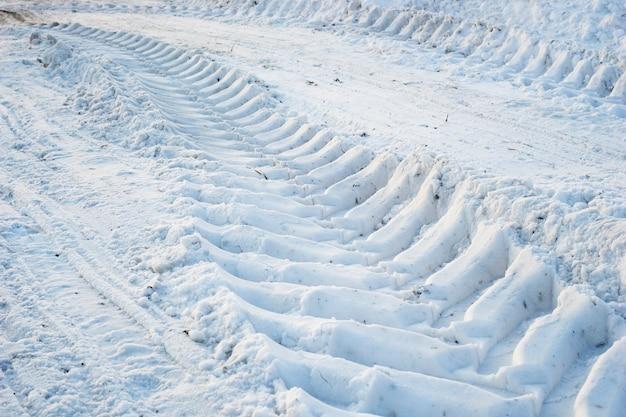 Odcisk bieżnika kół ciągnika na śniegu.