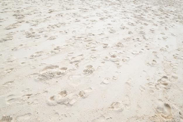 Odcisk stopy na białym piasku przy plażą w zmierzchu