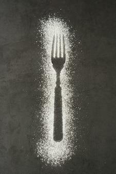 Odcisk widelec sylwetka wykonana z mąki na czarnym tle
