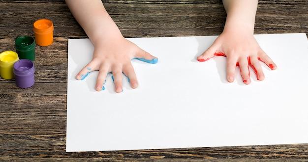Odciski palców dziecka na białej kartce papieru podczas rysowania dłońmi dziecka wielobarwnymi farbami