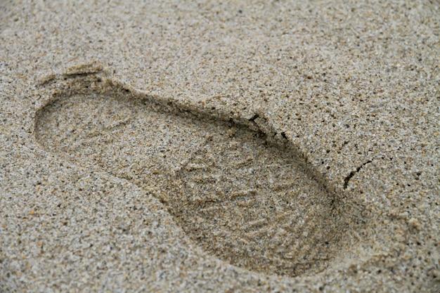 Odciski stopy na piasku na morzu