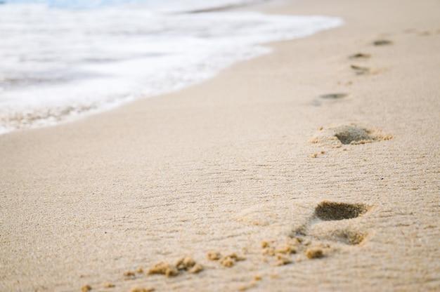 Odciski stopy w piasku przy zmierzchem