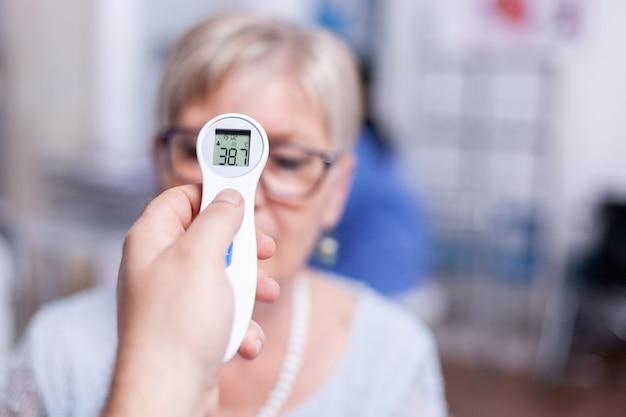 Odczyt temperatury ciała za pomocą termometru na podczerwień podczas badania lekarskiego