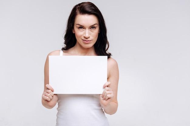 Oddana elegancka kobieta pozująca z pustą kartką papieru, równość społeczna