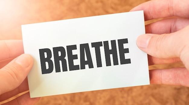 Oddychaj napis słowo na białej kartce papieru w rękach biznesmena