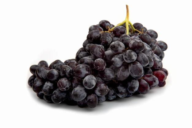 Oddział czarnych winogron z kroplami poziomo na białym tle