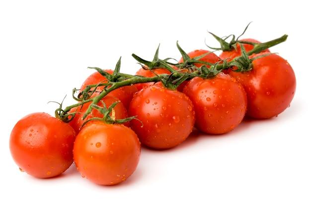 Oddział dojrzałych pomidorów cherry na białym tle, z bliska.