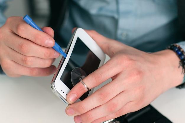 Oddzielanie ekranu smartfona w warsztacie.