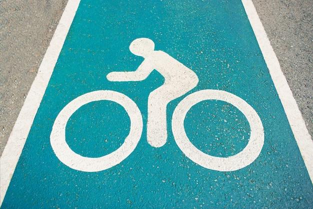 Oddzielny pas rowerowy do jazdy na rowerze. ikona roweru na pasie. nowy publiczny asfaltowy pas rowerowy z bliska przy drodze. biały lakierowany rower na asfalcie.