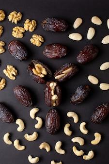 Odgórnego widoku arachidów xurma brąz odizolowywający na ciemnej podłoga