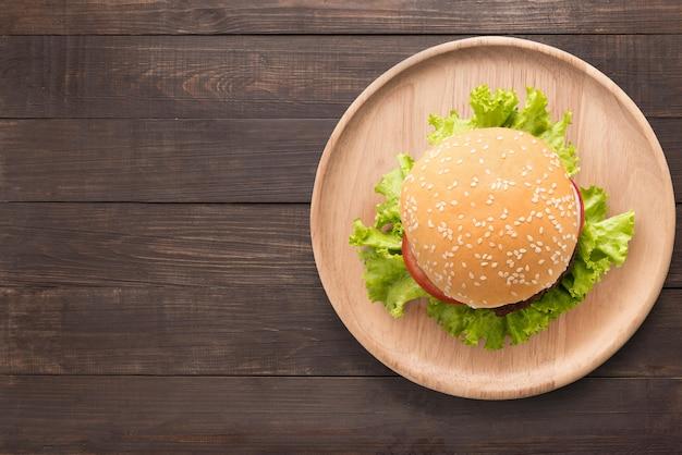 Odgórnego widoku bbq hamburger na drewnianym naczyniu na drewnianym tle. skopiuj miejsce na tekst