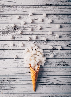Odgórnego widoku białego cukieru sześciany w lody gofrze na białym drewnianym stole. pionowy
