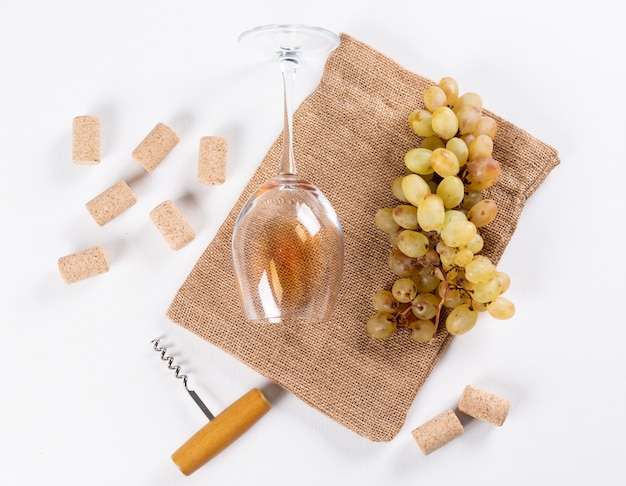 Odgórnego widoku biały wino w szkle z winogronem na bieliźnianej torbie na biały horyzontalnym