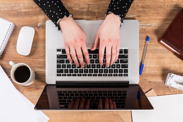Odgórnego widoku biznesowa kobieta pracuje na jej laptopie
