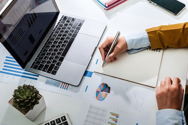 Odgórnego widoku bizneswoman pracuje na biurku używać kalkulatora i laptopu analizuje finansową księgowość w biurze