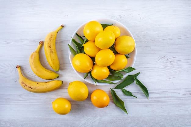 Odgórnego widoku cytryny w talerzu i bananach na białej drewnie ukazują się