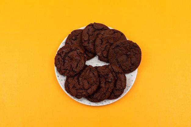 Odgórnego widoku czekoladowi ciastka na kolor żółty powierzchni