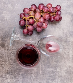 Odgórnego widoku czerwone wino w szkłach i winogronie na zmroku kamiennym vertical